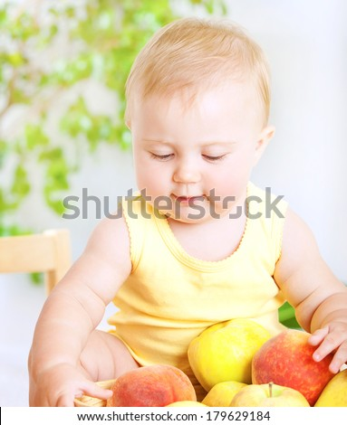 Happy little baby girl eating fresh tasty fruits for lunch, enjoying healthy food at home, organic nutrition for kids - stock photo