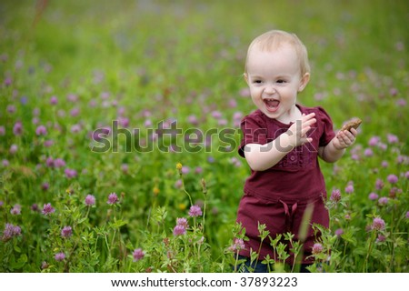 Happy little baby girl in a meadow eating cookie - stock photo