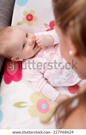 Happy little baby girl lying on back, smiling at mother. - stock photo