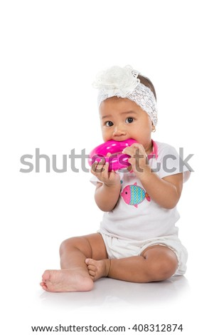 happy little baby girl put a toy in her mouth while sitting on the floor isolated on a white background - stock photo
