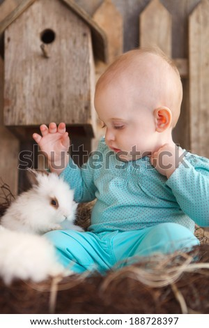 Happy little baby girl with a small white rabbit on the wooden background