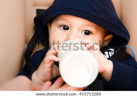 happy little baby sitting in a stroller and drinking from a bottle of milk, in winter clothes. The first   child eat nutritious snacks. Asian, black eyes
