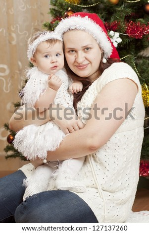Happy little baby with her mother sitting under the christmas tree