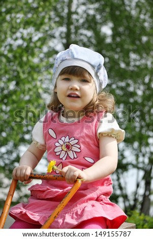 Happy little beautiful girl in pink dress sits on orange seesaw at summer day.