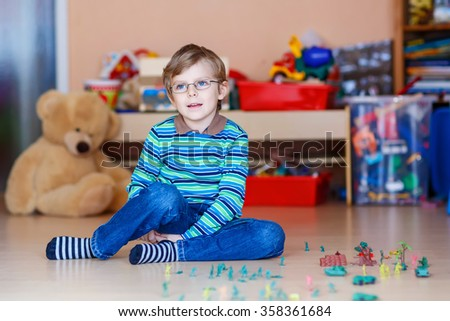 Happy little blond child playing with lots of small toy soldiers, indoor. Active kid boy with glasses wearing colorful shirt and having fun at home or at nursery. - stock photo