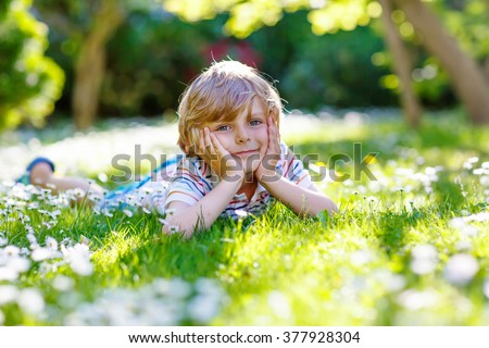 Happy little blond child with blue eyes laying on the grass with daisies flowers in the park. On warm summer day during school holidays. Kid boy dreaming and smiling. - stock photo