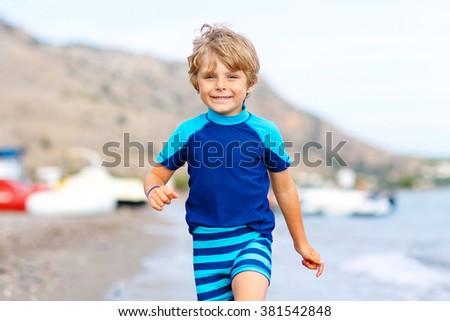 Happy little blond kid boy running on ocean beach. Child having fun. Vacations, summer, travel concept. Funny preschooler enjoying summer vacations on sea. - stock photo