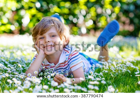 Happy little blond kid boy with blue eyes laying on the grass with daisies flowers in the park. On warm summer day during school holidays. Child dreaming and smiling.