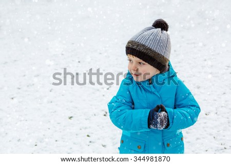 Happy little blond toddler boy walking on cold day in blue coat. Funny kid wearing warm clothes on winter day Carefree childhood. Child having fun with snow - stock photo