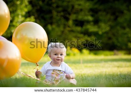 Happy little blonde caucasian girl outside with yellow and pink balloons playing and having fun - stock photo