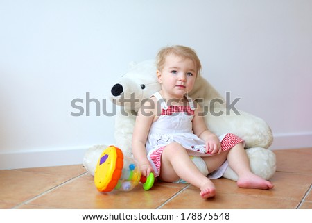 Happy little blonde toddler girl playing indoors at home or kindergarten sitting on the tiles floor against a white wall bending on a big white teddy bear