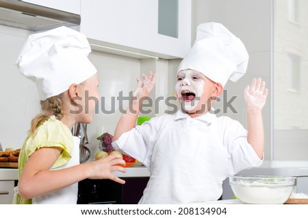 Happy little boy and girl baking in the kitchen in their cute white chefs uniforms laughing and fooling around with flour on their faces - stock photo