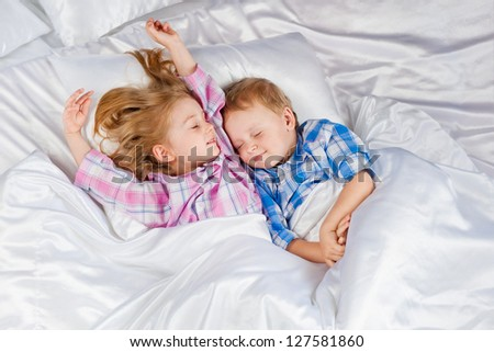 Happy little boy and girl in bed - stock photo