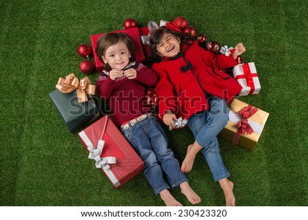 Happy little boy and girl lying on the floor surrounded by Christmas presents - stock photo