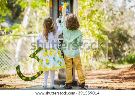 Happy little boy and girl playing with the phone in the park. - stock photo