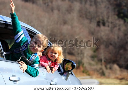 happy little boy and girl travel by car