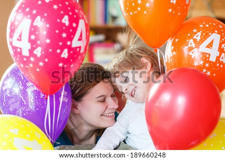 Happy little boy and his mother celebrating his 4 birthday with colorful balloons, indoor in kids room. - stock photo