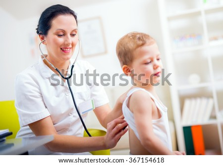 Happy little boy at the doctor for a checkup - being examined with a stethoscope - stock photo