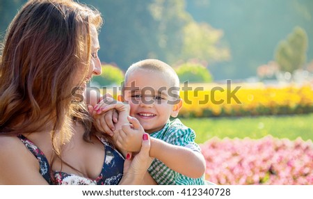 Happy little boy being embraced by his mother infront of a springtime blossom of a park.