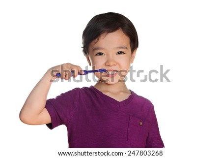 Happy little boy brushing teeth, isolated on white. Toddler in purple shirt on white background exercising dental hygiene.  Child brushing teeth. Young kid happy to brush his teeth. Dental smiles. - stock photo