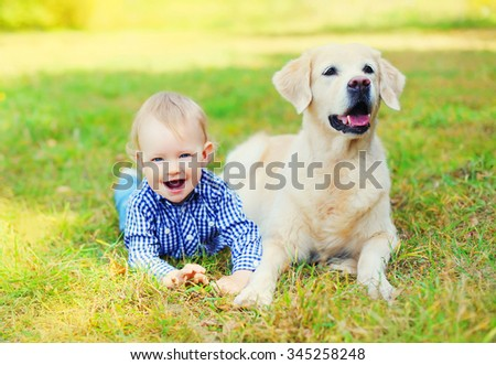 Happy little boy child and Golden Retriever dog lying together on grass in park
