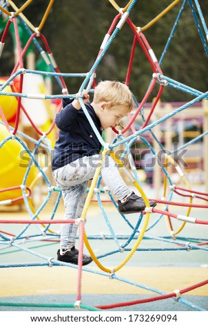 Happy little boy climbing on playground equipment as he enjoys the adventure and exercise - stock photo