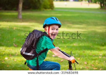 Happy little boy cycling in summer park - stock photo