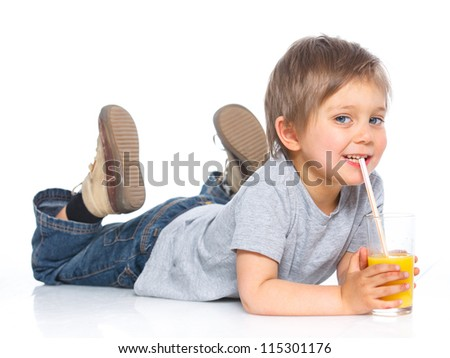 Happy little boy drinking orange juice. Isolated over white background.