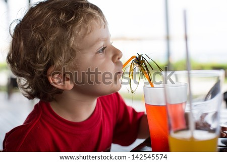 Happy little boy drinking orange juice with straw in summer garden