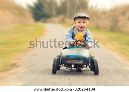 Happy little boy driving big vintage old toy car and having fun, outdoors. Kid leisure on autumn day