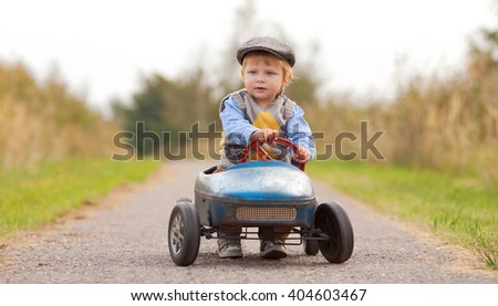 Happy little boy driving big vintage old toy car and having fun, outdoors. Kid leisure on summer day