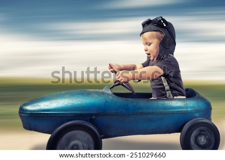 Happy little boy driving big vintage old toy car and having fun, outdoors. Kids leisure on summer day - stock photo