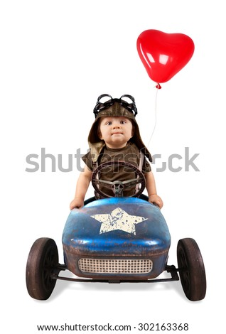 Happy little boy driving big vintage old toy car with red heart balloon and having fun, isolated on white - stock photo