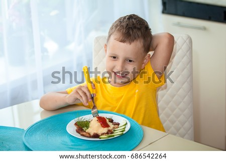 Happy little boy eating a healthy dinner at the table
