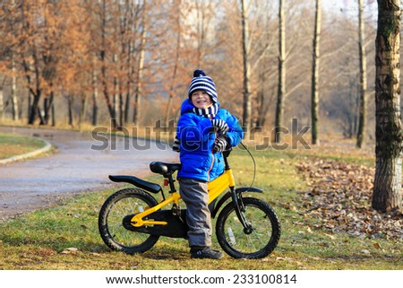 happy little boy enjoying bike ride in autumn park - stock photo