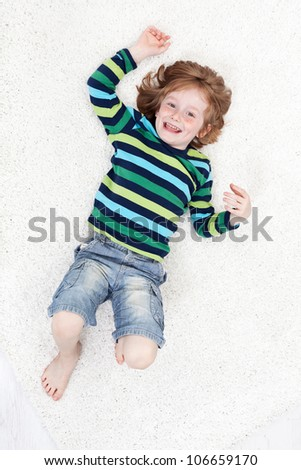 Happy little boy having fun laughing on the floor - top view - stock photo