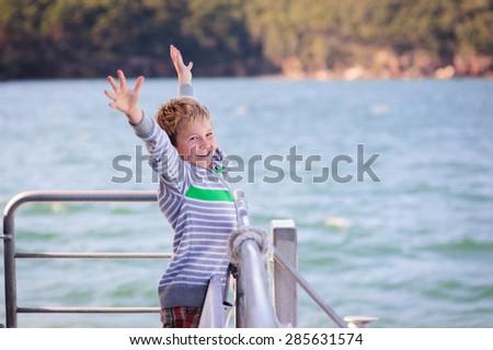 Happy little boy having fun on a boat or ferry in the ocean sea - stock photo