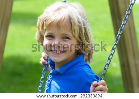 Happy little boy having fun on a swing outdoor - stock photo