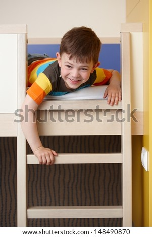 Happy little boy having fun on bunk bed, laughing.