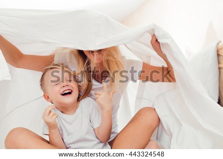 Happy little boy having fun with his mother in bed under the blanket - stock photo