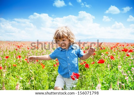 Happy little boy in blue short running in poppy red flowers field in france - stock photo