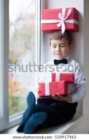 happy little boy in bow tie sitting by window with a gift box on his head and two gift boxes in hands closing his eyes