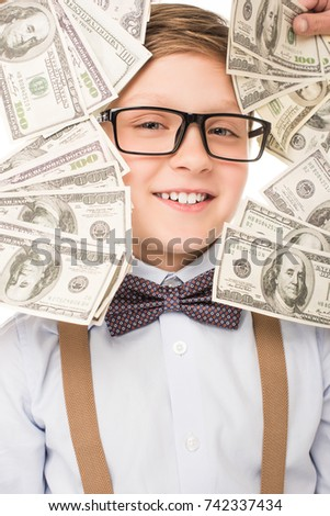 happy little boy in eyeglasses smiling at camera between dollar banknotes
