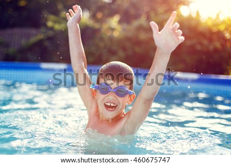 Happy little boy in goggles enjoying play in pool, hurray, summer holiday