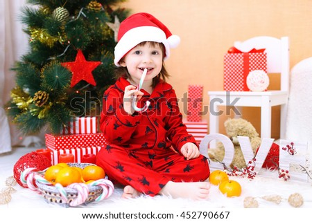 Happy little boy in Santa hat with lollipop and presents sitting near Christmas tree