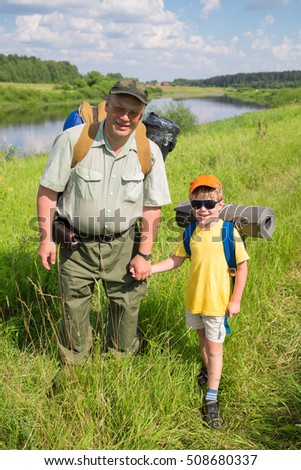Happy little boy in sunglasses and father stand near river during hike at summer day