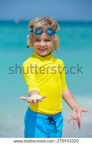 Happy little boy in swimming goggles and seashell at a tropical beach - stock photo