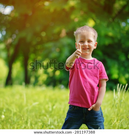 Happy little  boy  in the park. On warm sunny   summer day. Kid  smiling, shows a class - stock photo