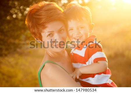 happy little boy in the park with mother - stock photo