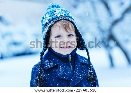 Happy little boy in winter clothes with falling snow. Kid enjoying and catching snowflakes, outdoors on cold day. - stock photo